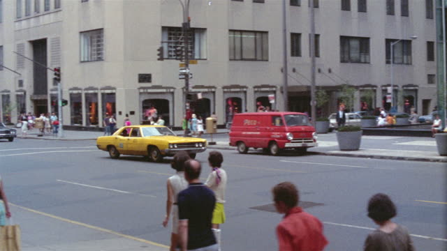 1969 ws pan yellow taxi driving past bonwit teller department store, down 5th avenue from east 56th to east 55th street/ manhattan, new york, usa - anno 1969 video stock e b–roll