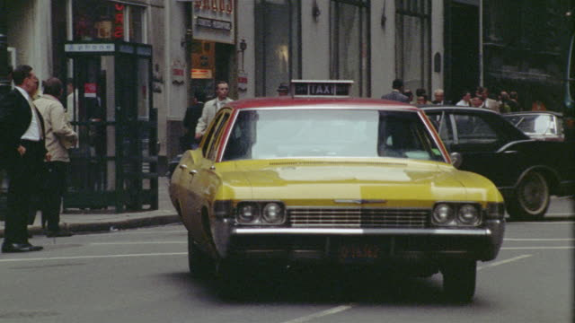 1969 WS ZO PAN Yellow taxi pulling out from kerb and driving down street / Manhattan, New York