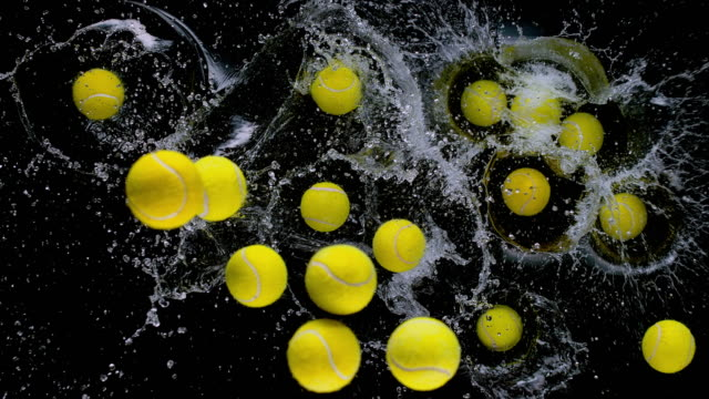 slo mo ld yellow tennis balls falling into water on black background - large group of objects stock videos & royalty-free footage