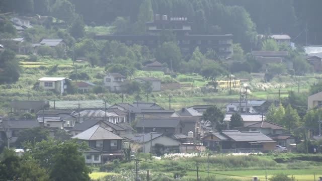 a yellow train on the kyudai main line running through rustic scenery in the city of yufu - oita city stock videos & royalty-free footage