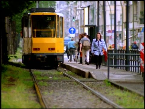 yellow tram departs from tram stop, berlin - tram stock videos & royalty-free footage
