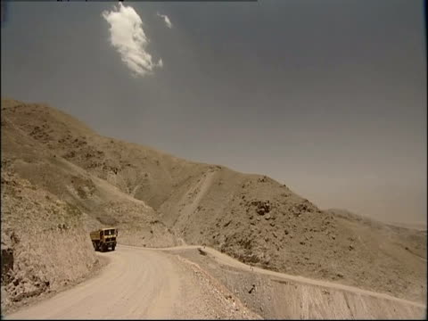 A yellow truck drives through the desert.