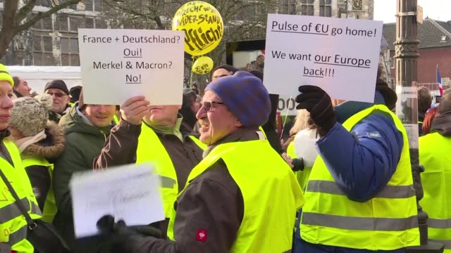 Yellow vest demonstrators gather to greet French President Emmanuel Macron with jeers as he arrives at the Aachen town hall to sign a Franco German...