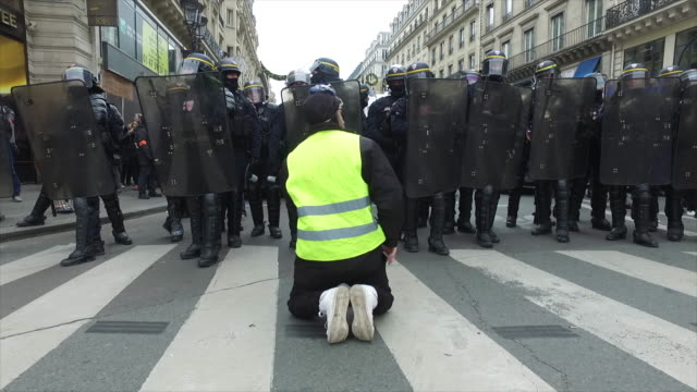 yellow vest kneeling in front of the police and gendarmerie place de l'opera - manifestante video stock e b–roll