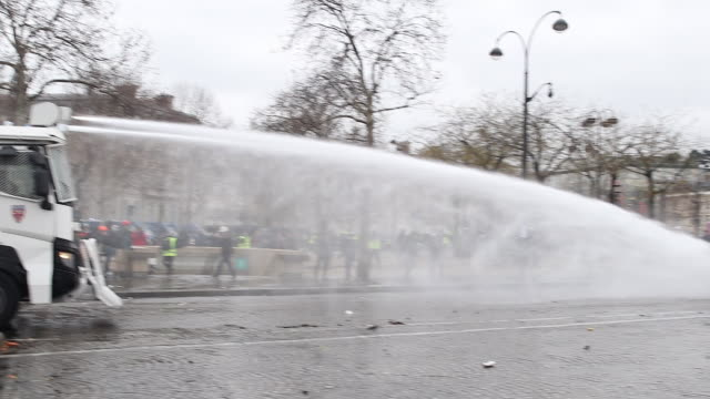 yellow vests and police and gendarmerie forces. use of water cannon and tear gas in front of the triumphal arch - water cannon stock videos & royalty-free footage