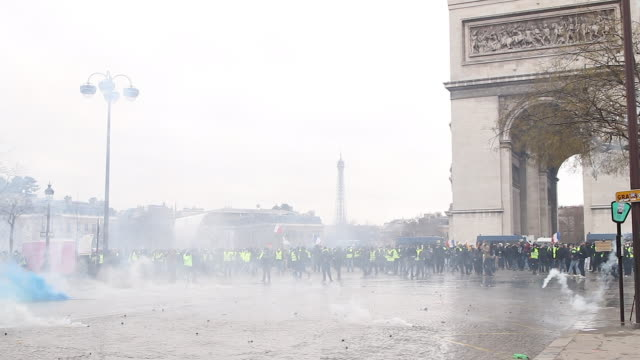 yellow vests and police and gendarmerie forces use Tear gas a protester launches a pavement