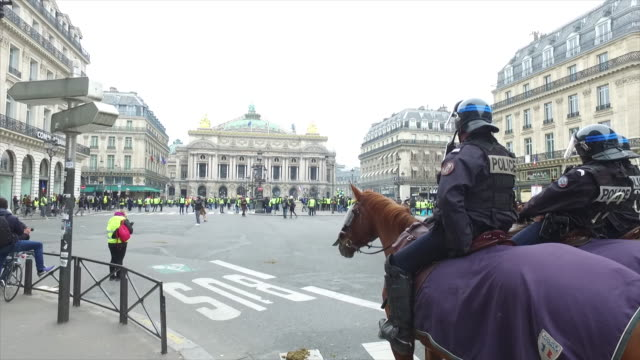 yellow vests place de l'opera in front of policemen with horses - place de l'opera stock videos and b-roll footage
