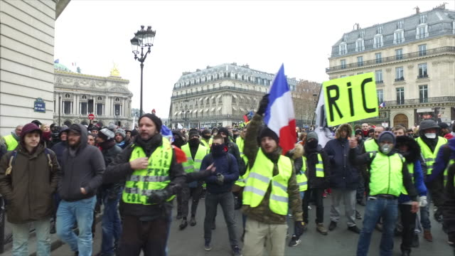 yellow vests place de l'opera in front of the police and gendarmerie a sign where is written ric - vest stock videos & royalty-free footage
