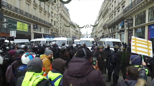 yellow vests place de l'opera in front of the police and gendarmerie a sign where is written ric - place de l'opera stock videos and b-roll footage