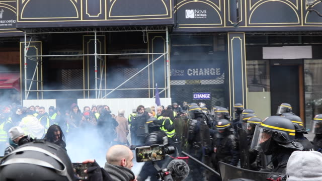 yellow vests place de l'opera in front of the police and gendarmerie with tear gas - 対決点の映像素材/bロール