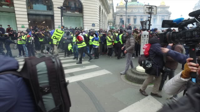 yellow vests place de l'opera in front of the police and gendarmerie with tear gas and a sign where is written ric citizens' initiative referendum - place de l'opera stock videos and b-roll footage
