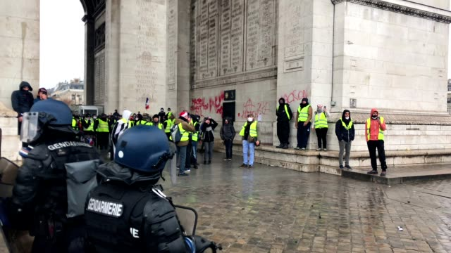 vídeos de stock, filmes e b-roll de yellow vests protest near champs-elysées in paris france against macron. - arco triunfal