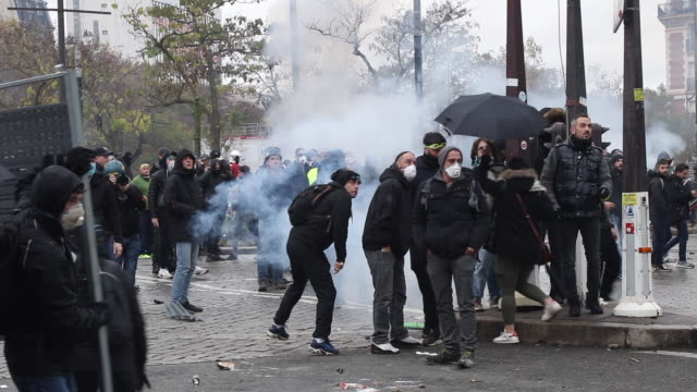 yellow vests' protesters set up barricade. demonstrator throwing stones at police. place of italy during a protest to mark the first anniversary of... - 公共物破壊点の映像素材/bロール