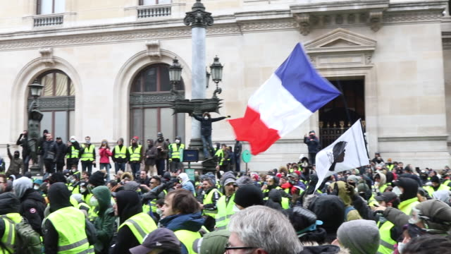 yellow vests with french flags place de l'opera in front of the police and gendarmerie - place de l'opera stock videos and b-roll footage