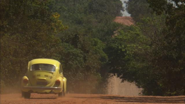 vídeos de stock, filmes e b-roll de a yellow volkswagen beetle drives away on a dusty  road. - estrada rural