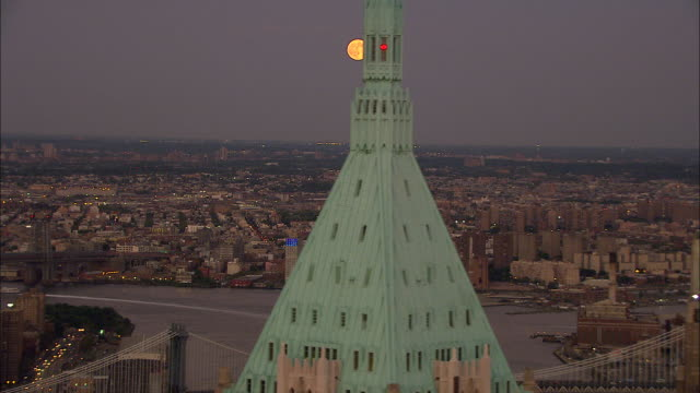 Yellowcolored Moon in distant over Queens cityscape passing partial Manhattan skyscrapers building tops in FG NYC
