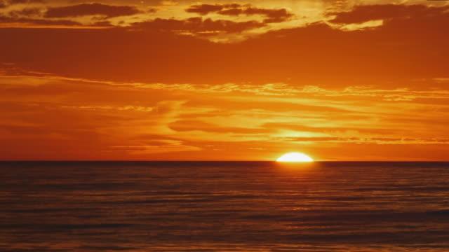 tl yellow/orange sun rising over atlantic ocean, clouds overhead, cape cod national seashore, massachusetts - horizon over water stock-videos und b-roll-filmmaterial