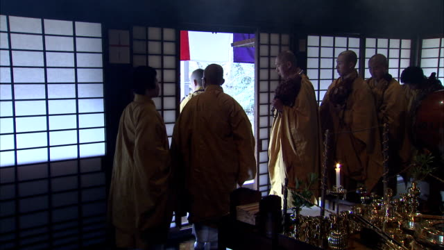 yellow-robed shinto monks walk out of a shrine. available in hd. - shinto stock videos & royalty-free footage