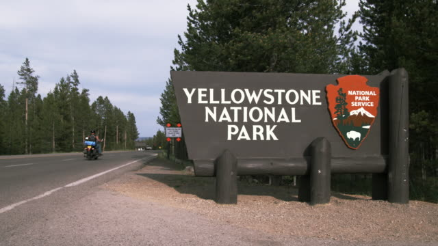 WS Yellowstone National Park sign on roadside / Yellowstone, Wyoming, USA