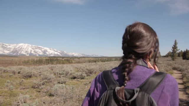 vidéos et rushes de yellowstone np woman walks forest trail geothermal location - allée couverte de planches