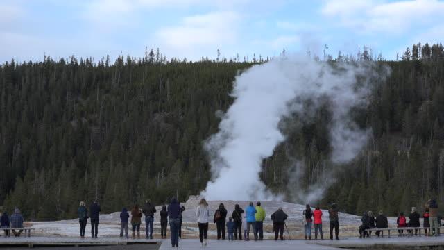 stockvideo's en b-roll-footage met yellowstone old faithful people watching start of eruption - old faithful geiser