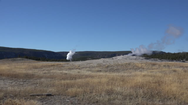yellowstone old faithful steaming and distant geyser - old faithful stock videos & royalty-free footage