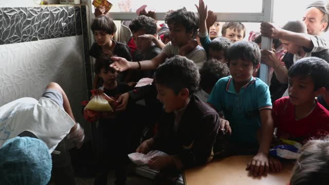 yemeni children from families who were affected by the war and blockade, wait to receive a lunch meal from a charitable center on april 12, 2021 in... - exclusive stock videos & royalty-free footage