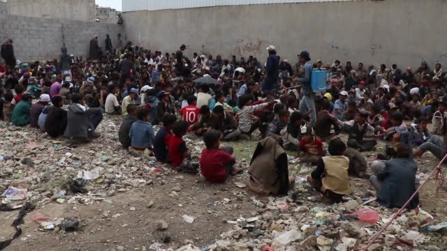 yemeni people who were affected by the ongoing war wait to receive dinner from a charity organization during the muslim's fasting month of ramadan on... - yemen stock videos & royalty-free footage