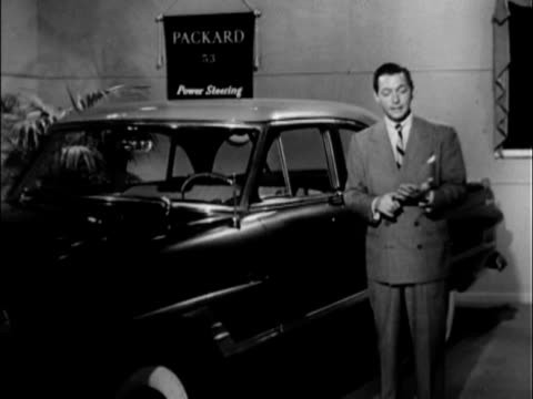 yes look to packard for the easiesthandling car ever built the oncamera announcer says packard's power steering is shown to help parking to help... - 1953年点の映像素材/bロール