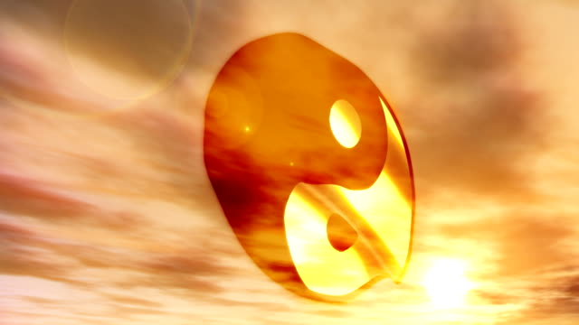 A yin yang symbol waves in the wind against a beautiful sunset.