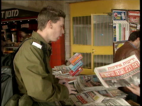 stockvideo's en b-roll-footage met yigal amir trial / assassination video released itn israel tel aviv soldier buying newspaper with photograph of the moment of the shooting - yitzhak rabin