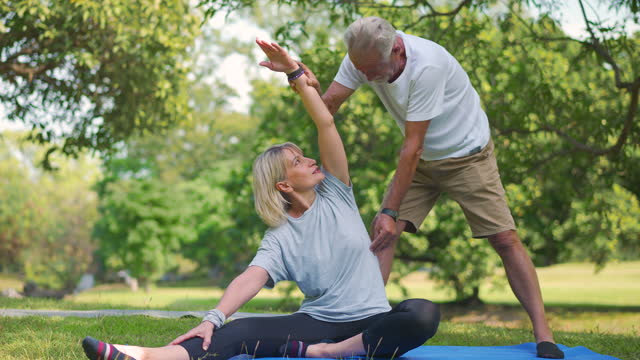 yoga at park. senior family couple exercising outdoors. concept of healthy lifestyle. - grey hair stock videos & royalty-free footage
