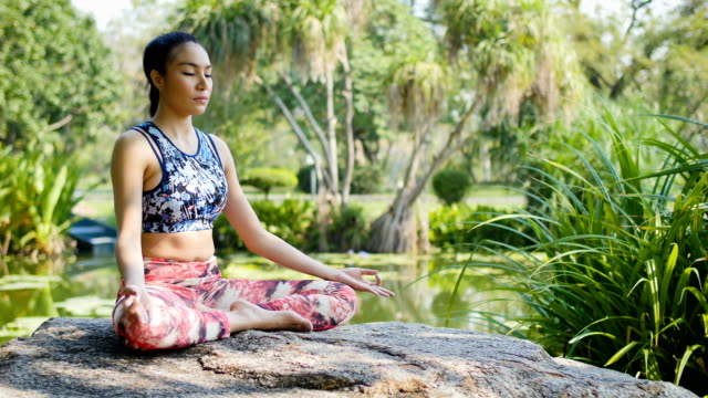 yoga at park, young asian woman in pose sitting  lotus position and meditation - lotus position stock videos & royalty-free footage