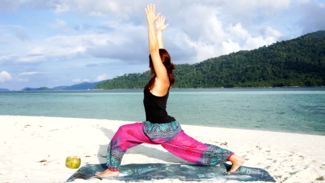 Yoga at tropical beach. Colorful pants and fresh coconut