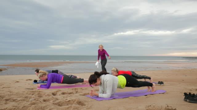 yoga beach class - recreational pursuit stock videos & royalty-free footage