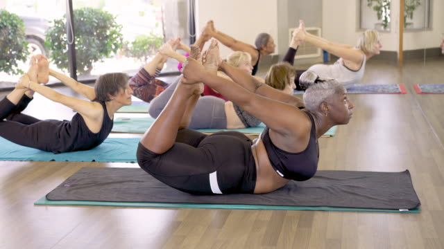 yoga class doing bow pose - overweight yoga stock videos & royalty-free footage