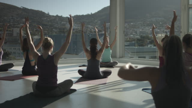 yoga class doing stretching exercises, in rooftop studio - mindfulness stock videos & royalty-free footage