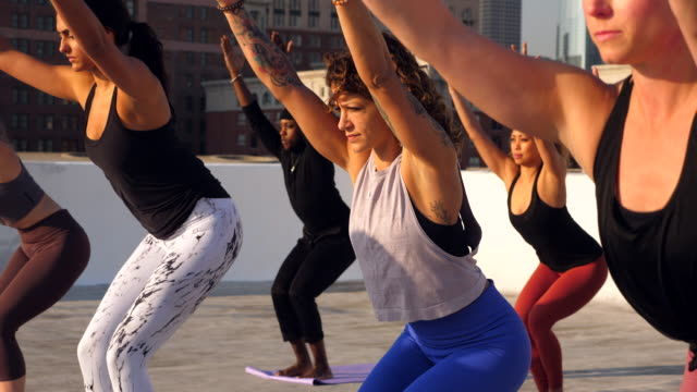 ms yoga class in chair pose while practicing on rooftop overlooking city - tights stock videos & royalty-free footage