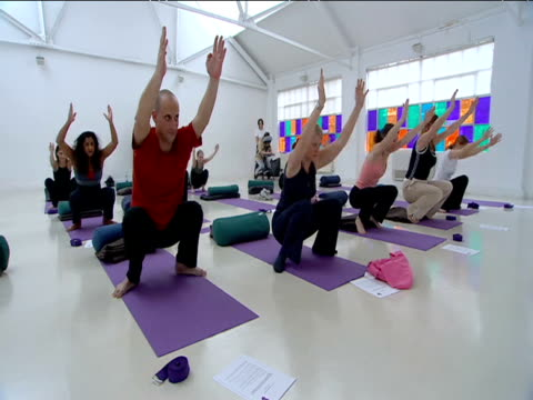 Yoga class in chair position during lesson in bright studio