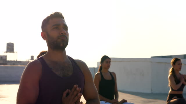 ms yoga class in lotus position during sunset class on rooftop - lotus position stock videos & royalty-free footage
