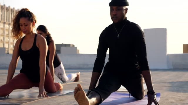 vidéos et rushes de ms pan yoga class in monkey pose while practicing on rooftop - petit groupe de personnes