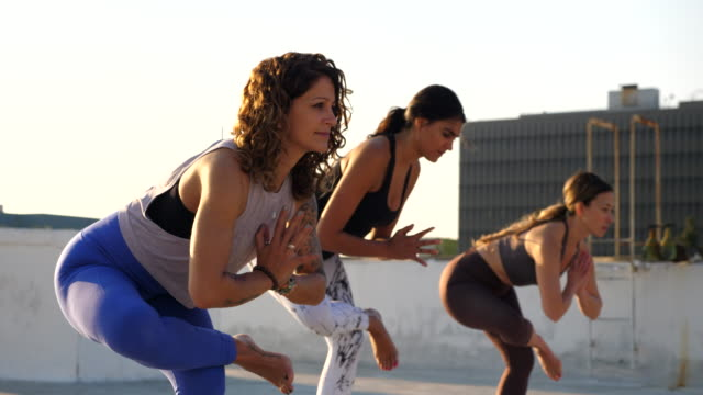 ms yoga class in standing figure four pose during class on rooftop - tights stock videos & royalty-free footage