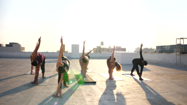 ms yoga class in triangle pose during rooftop class at sunset - tights stock videos & royalty-free footage
