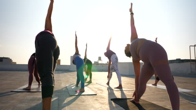 ms pan yoga class in triangle pose while practicing on rooftop at sunset - tights stock videos & royalty-free footage