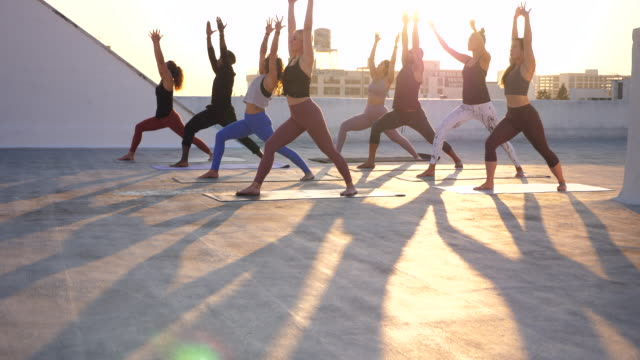 ms tu yoga class moving through warrior pose during sunset rooftop workout session - small stock videos & royalty-free footage