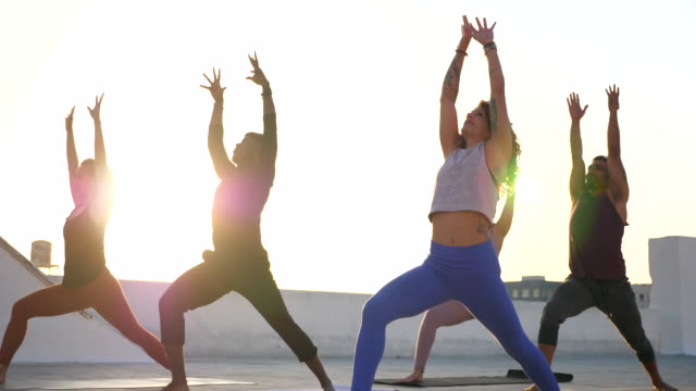 ms yoga class moving through warrior pose during sunset rooftop workout session - trousers stock videos & royalty-free footage
