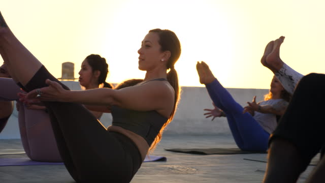 ms pan yoga class on rooftop at sunset - vest stock videos & royalty-free footage