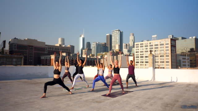ws yoga class on rooftop overlooking city - vest stock videos & royalty-free footage