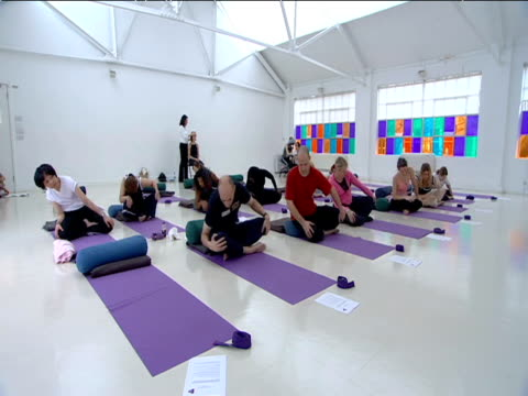 yoga class perform movements whilst in sitting posture - posture stock videos and b-roll footage