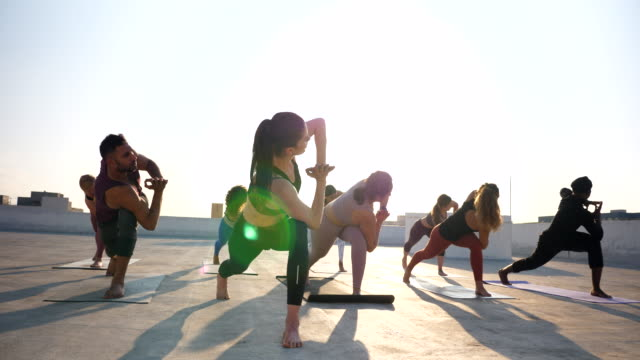 ms pan yoga class practicing on rooftop at sunset - tights stock videos & royalty-free footage